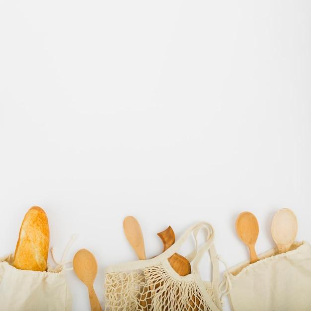 Bovenaanzicht van herbruikbare tassen met brood en houten lepels Gratis Foto