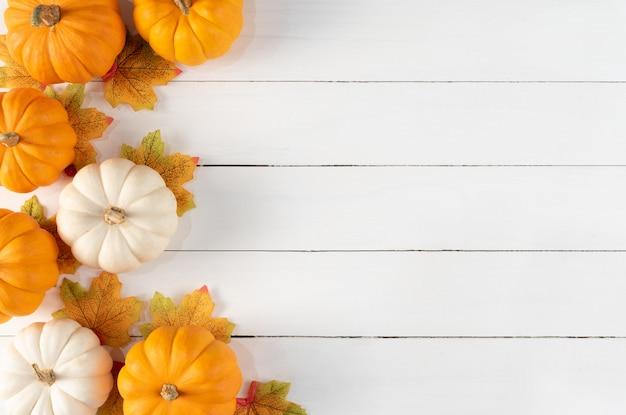 Bovenaanzicht van herfst esdoorn bladeren met pompoenen en rode bessen op witte houten achtergrond. thanksgiving day concept. Premium Foto