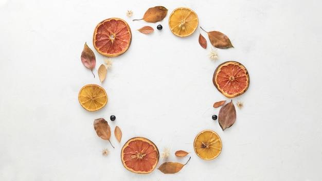 Bovenaanzicht van herfstbladeren met gedroogde citrus Gratis Foto