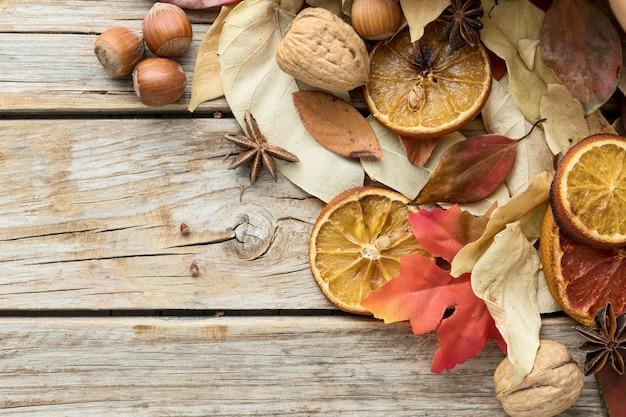 Bovenaanzicht van herfstbladeren met kastanjes en gedroogde citrus Gratis Foto