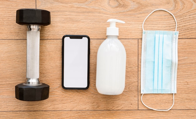 Bovenaanzicht van het gewicht met smartphone en handdesinfecterend middel Gratis Foto