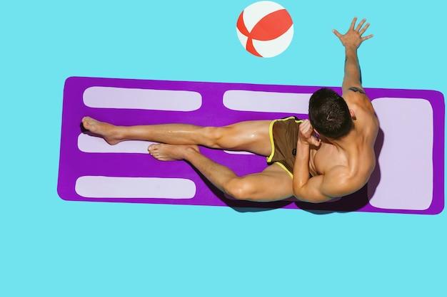 Bovenaanzicht van het jonge blanke mannelijke model rusten op strandresort op paarse mat Gratis Foto