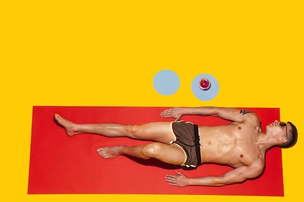 Bovenaanzicht van het jonge blanke mannelijke model rusten op strandresort op rode mat en geel Gratis Foto