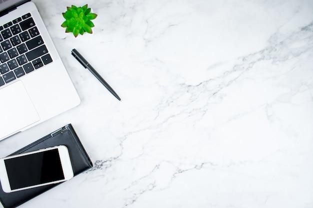 Bovenaanzicht van het moderne bureau van een jonge man met een laptop, smartphone, lederen tas en accessoires Premium Foto