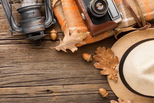 Bovenaanzicht van hoed en camera met herfstbladeren Gratis Foto