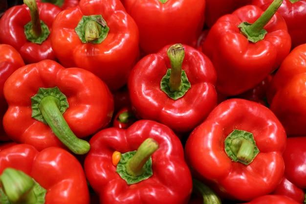 Bovenaanzicht van hoop van verse rijpe rode paprika met groene stam Premium Foto