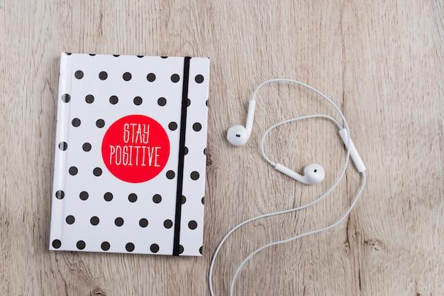 Bovenaanzicht van hotebook met polka dot cover en witte koptelefoon op houten tafel. minimale vlakligging. Premium Foto