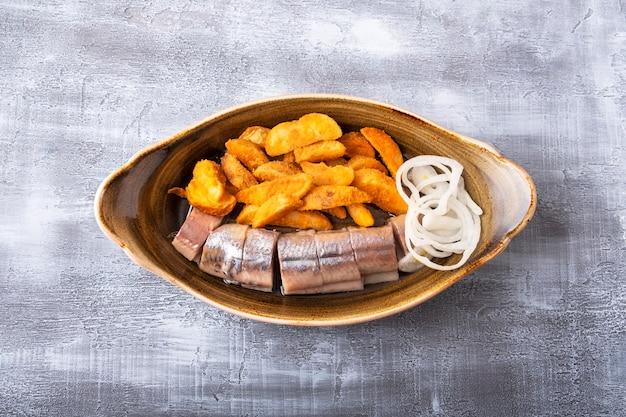 Bovenaanzicht van ingelegde haring en gebakken aardappel op een bord. kopieer ruimte Premium Foto