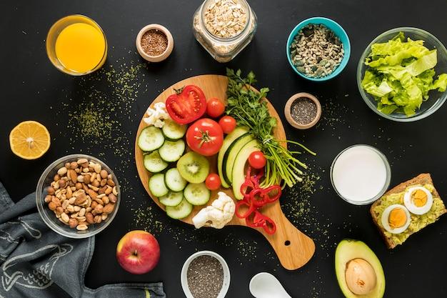 Bovenaanzicht van ingrediënten; dryfruits en groenten op zwarte achtergrond Gratis Foto