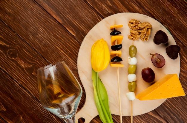 Bovenaanzicht van kaas ingesteld als cheddar en parmezaanse kaas met olijf walnoot druif en bloem op snijplank en leeg glas op houten achtergrond Gratis Foto