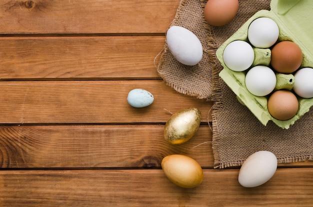 Bovenaanzicht van karton met gekleurde eieren voor pasen Gratis Foto
