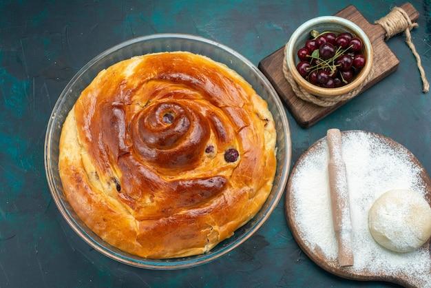 Bovenaanzicht van kersentaart met deegmeel en verse zure kersen op donkerblauw, taartcake zoet fruit Gratis Foto
