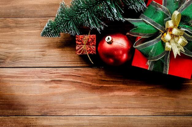 Bovenaanzicht van kerstmis achtergrond met ornamenten en geschenkdozen op de oude houten bord. Premium Foto