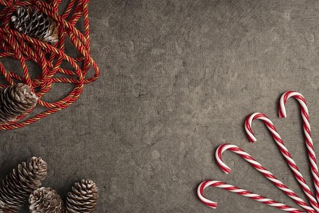 Bovenaanzicht van kerstmis achtergrond met zuurstokken en dennenappels Gratis Foto