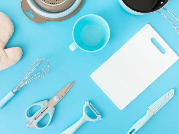 Bovenaanzicht van keuken kamer concept met keukengerei op blauwe tafel achtergrond. Premium Foto