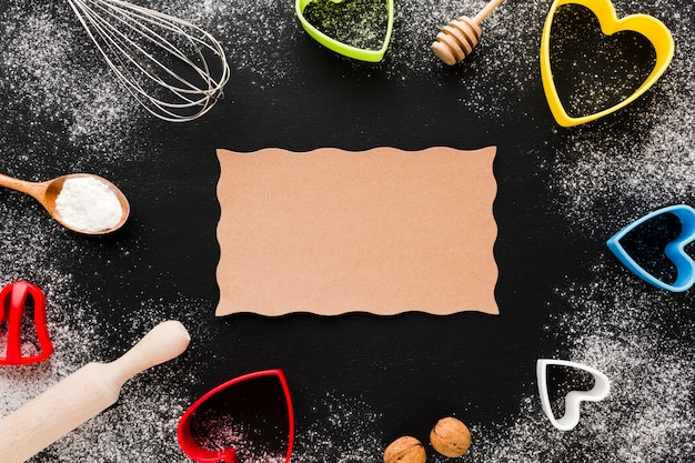 Bovenaanzicht van keukengerei en hartvormen met papier Gratis Foto