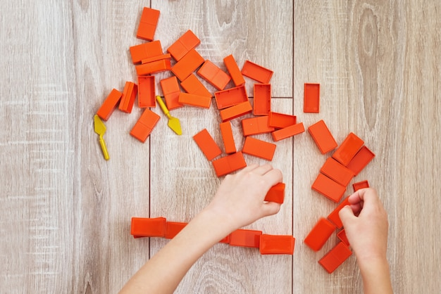 Bovenaanzicht van kind handen spelen met oranje speelgoed bakstenen. concept van kinderen lerning en onderwijs. baby vrije tijd met het ontwikkelen van speelgoed Premium Foto