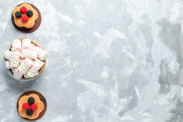 Bovenaanzicht van kleine cakes met marshmallows op lichte witte ondergrond Gratis Foto
