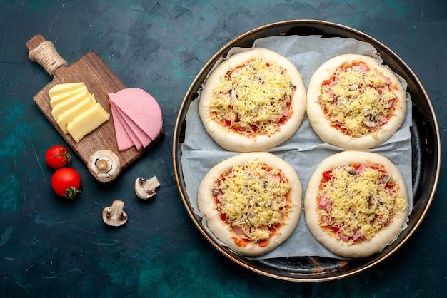 Bovenaanzicht van kleine rauwe pizza's deeg met groenten en kaas in pan op het donkerblauwe oppervlak Gratis Foto