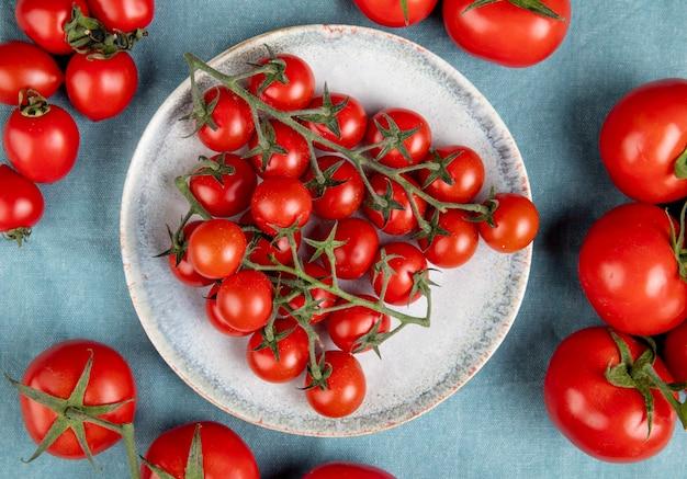 Bovenaanzicht van kleine tomaten in plaat met andere op blauw Gratis Foto