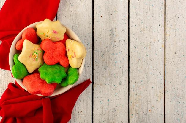 Bovenaanzicht van kleurrijke heerlijke koekjes verschillend gevormd binnen ronde plaat op het grijze oppervlak Gratis Foto