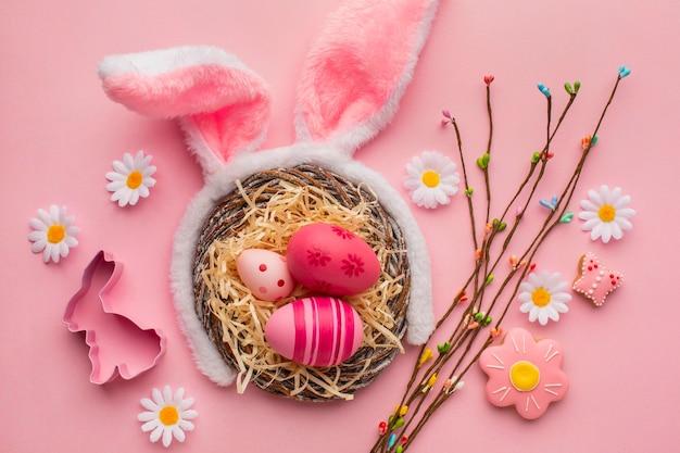 Bovenaanzicht van kleurrijke paaseieren in mand met bunny oren en kamille bloemen Premium Foto
