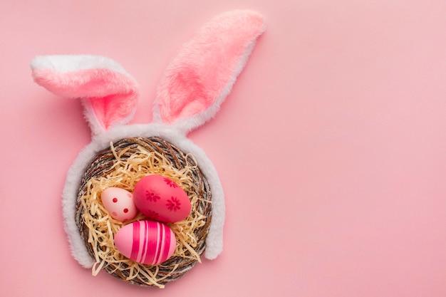 Bovenaanzicht van kleurrijke paaseieren in mand met konijnenoren en kopie ruimte Premium Foto