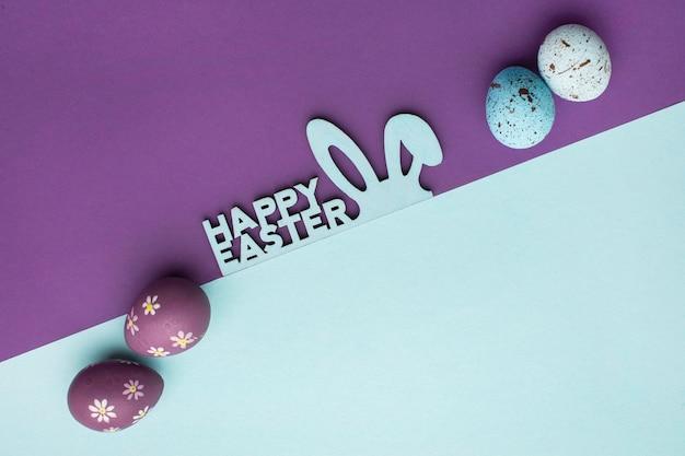 Bovenaanzicht van kleurrijke paaseieren met konijnenoren en groet Gratis Foto