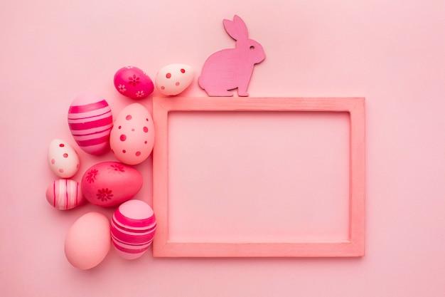 Bovenaanzicht van kleurrijke paaseieren met konijntje en frame Premium Foto