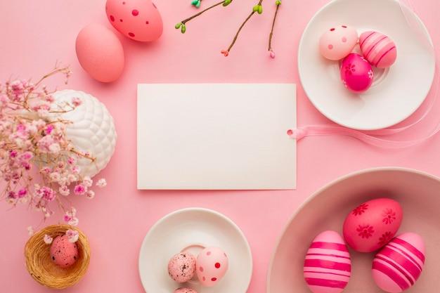 Bovenaanzicht van kleurrijke paaseieren op borden met papier en bloemen Premium Foto