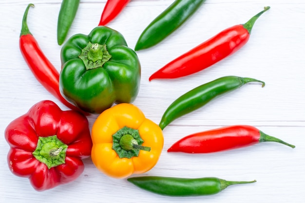 Bovenaanzicht van kleurrijke paprika's met pittige paprika's op licht bureau, plantaardig kruid warm voedsel maaltijd ingrediënt product Gratis Foto