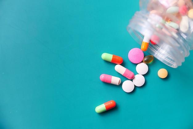 Bovenaanzicht van kleurrijke pillen morsen op groene achtergrond Premium Foto