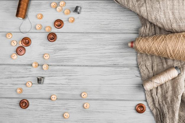 Bovenaanzicht van knop; string spool; naald; vingerhoedje en doek op houten achtergrond Gratis Foto