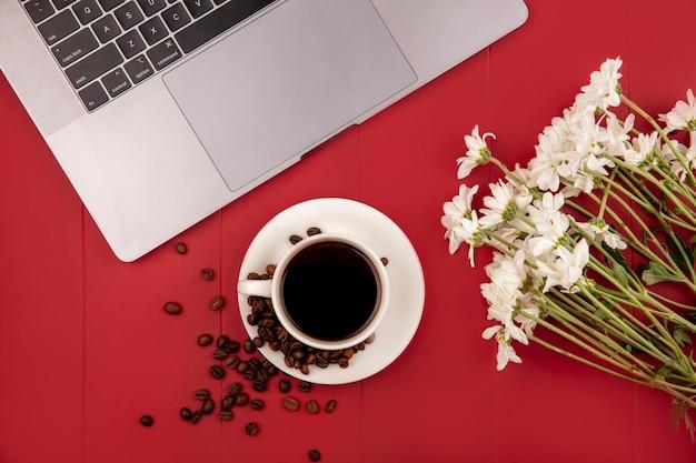 Bovenaanzicht van koffie op een witte kop met koffiebonen met witte bloemen op een rode achtergrond Gratis Foto