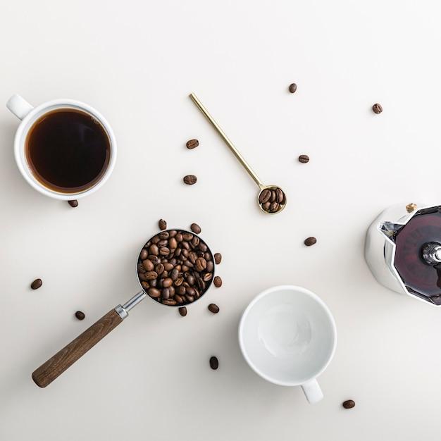 Bovenaanzicht van koffiebonen in beker met waterkoker en lepel Gratis Foto