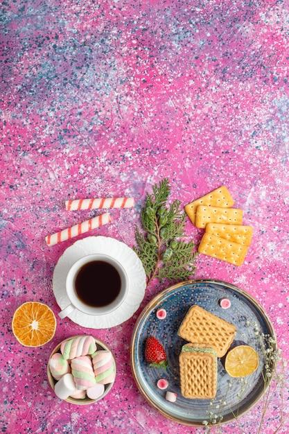 Bovenaanzicht van koffiekopje, koekjessandwiches, crackers en marshmallows Gratis Foto