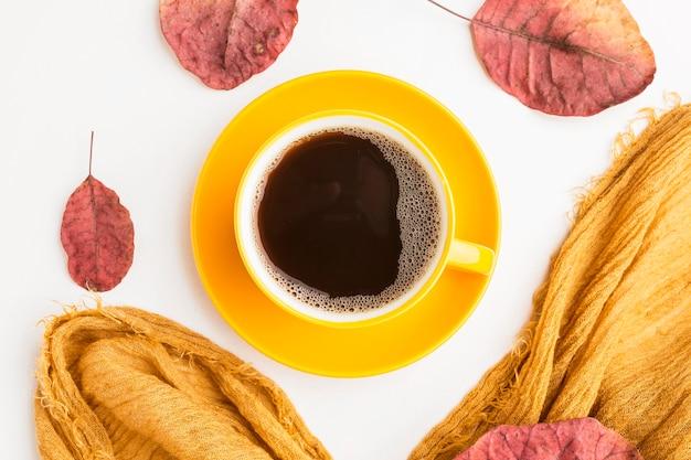 Bovenaanzicht van koffiekopje met herfstbladeren Gratis Foto