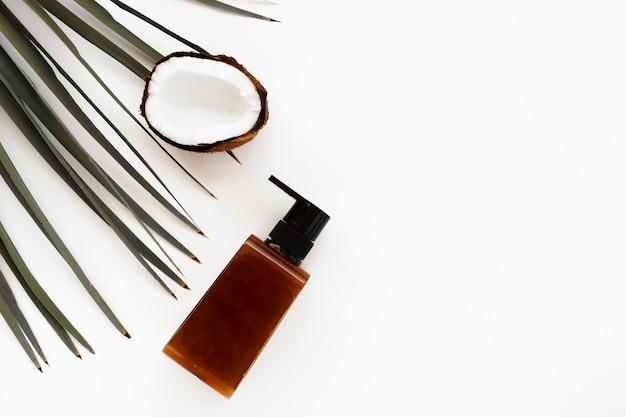 Bovenaanzicht van kokosnoot en etherische olie fles met kopie ruimte Gratis Foto