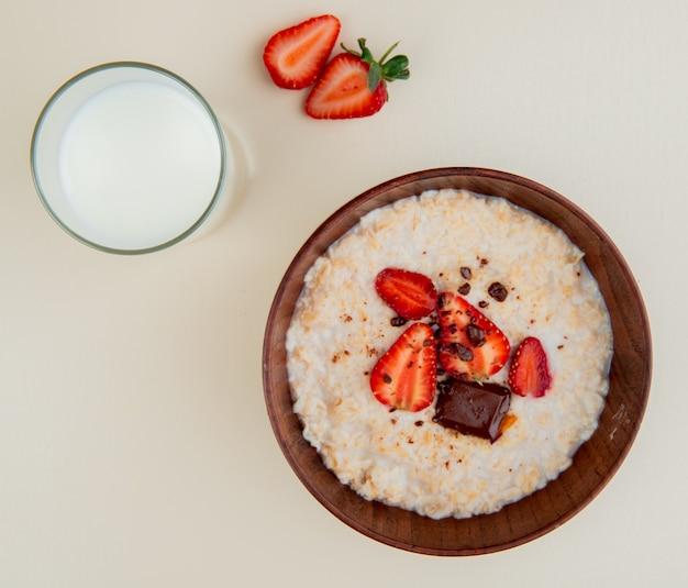 Bovenaanzicht van kom havermout met kwark chocolade en aardbeien met glas melk op witte ondergrond Gratis Foto