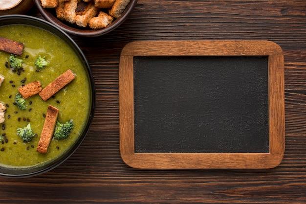 Bovenaanzicht van kom met winterbroccolisoep en schoolbord Gratis Foto