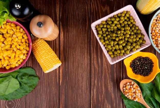 Bovenaanzicht van kommen van groene erwten maïs zaden en zwarte peper met spinazie op hout Gratis Foto