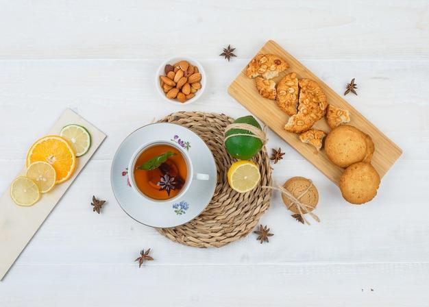 Bovenaanzicht van kopje thee en citrusvruchten op ronde placemat met koekjes op een snijplank, citrusvruchten en een kom met amandelen op witte ondergrond Gratis Foto