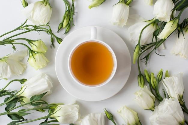 Bovenaanzicht van kopje thee met bloemen Gratis Foto