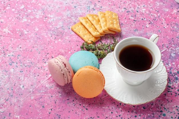 Bovenaanzicht van kopje thee met lekkere franse macarons op de roze muur Gratis Foto