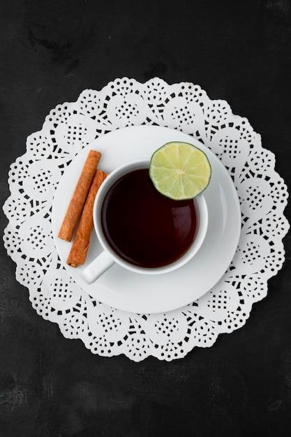 Bovenaanzicht van kopje thee met limoen en kaneel op theezakje op papier kleedje op zwarte ondergrond Gratis Foto