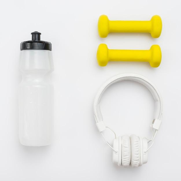 Bovenaanzicht van koptelefoon met fles water en gewichten Gratis Foto