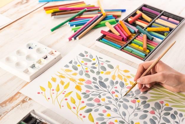 Bovenaanzicht van kunstenaar tekening bloemen ontwerp op werkplek Gratis Foto