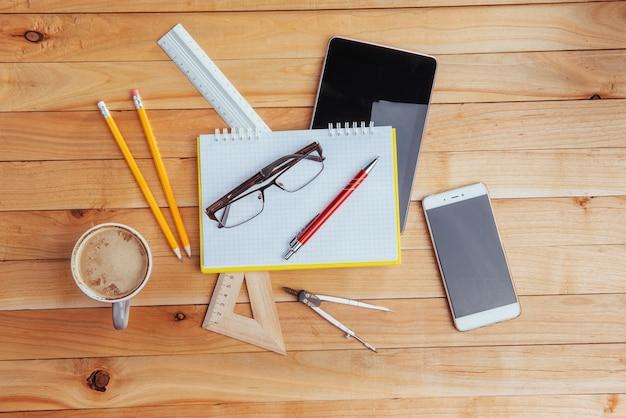 Bovenaanzicht van laptop, briefpapier, tekengereedschappen en een paar glazen. improviseren. Premium Foto