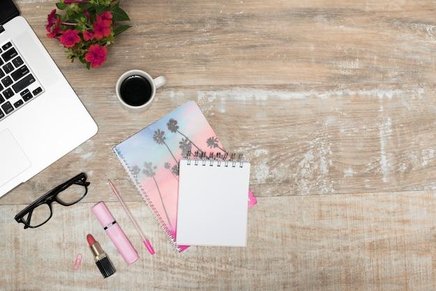 Bovenaanzicht van laptop; lippenstift; markeerstift; spiraalvormige blocnote; koffiekop; pen; en lenzenvloeistof op houten bureaulijst Gratis Foto
