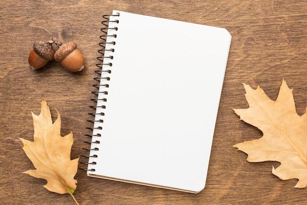 Bovenaanzicht van laptop met herfstbladeren en eikels Premium Foto